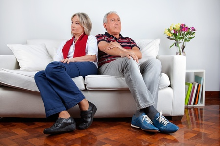 mid adult male: Full length of senior couple sitting on sofa after quarrel Stock Photo
