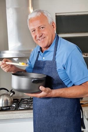 味の食べ物にスプーンを保持笑みを浮かべてシニア男の肖像