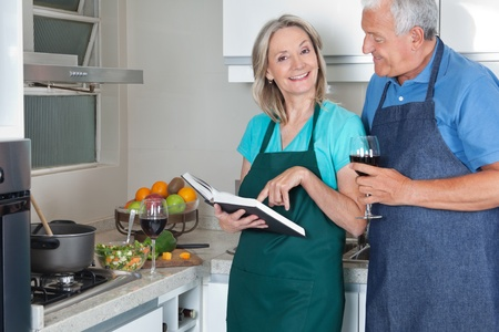 Portrait of smiling woman with recipe book and man holding wine glass in kitchen photo