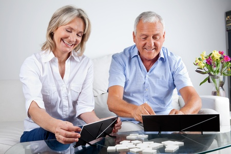 rummy: Happy senior couple playing rummy together at home.