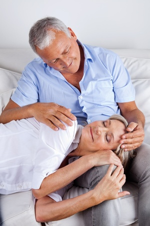 mid adult male: Relaxed woman asleep on husbands lap