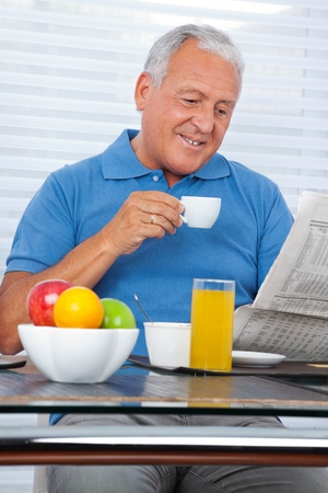Smiling senior man reading newspaper while having breakfast at home photo