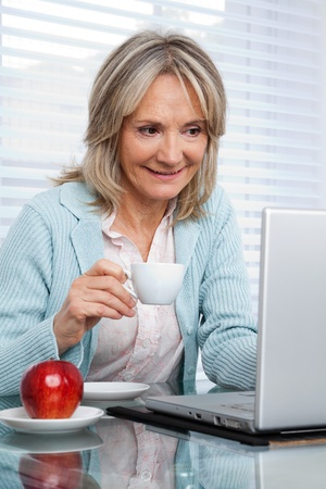 Smiling mature woman working on laptop while having cup of tea photo