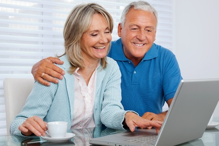 Mature woman having tea and browsing internet with her husband on laptop photo