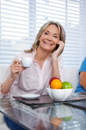 middle aged women: Portrait of mature woman talking on cell phone while having a cup of tea