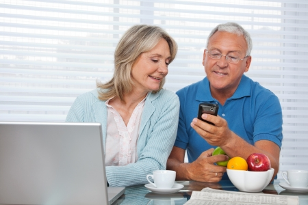 Senior man showing mobile phone to female Stock Photo