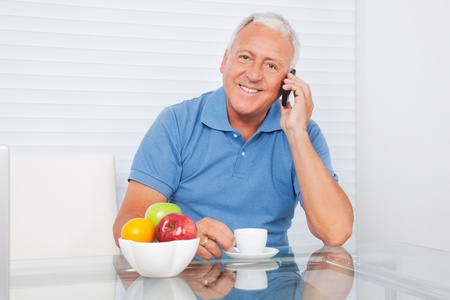Portrait of smiling senior man talking on cell phone while having tea photo