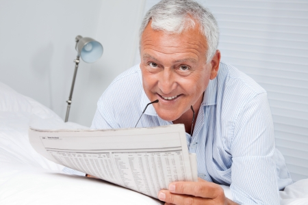Portrait of senior man reading newspaper lying on bed at home photo