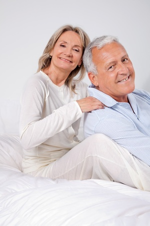 Portrait of happy couple sitting together on bed at home photo
