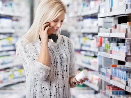farmacia: Mujer con envase de la medicaci�n mientras se habla por tel�fono celular Foto de archivo