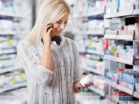 Woman holding medication container while talking on cell phone photo
