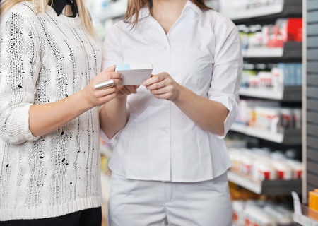 Mid-section of female pharmacist advising customer how to take medicine Stock Photo - 11702408