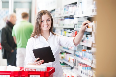 Portrait of female pharmacist holding tablet PC standing by the shelf at drugstore photo
