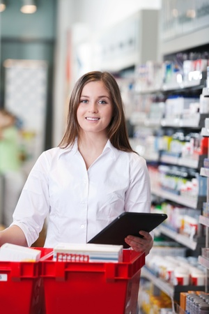 Portrait of smiling female pharmacist holding tablet PC photo