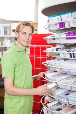 Portrait of smiling man holding medicine box at drugstore Stock Photo - 11702274