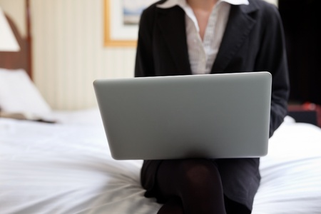 Cropped image of business woman working on laptop while sitting on bed photo