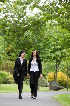walking in park: Full length of two female executives walking in park