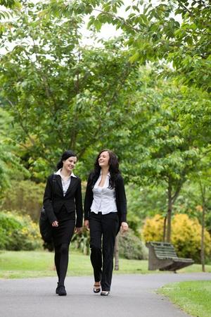 caminando: Longitud total de dos ejecutivos de las mujeres caminando en el Parque Foto de archivo
