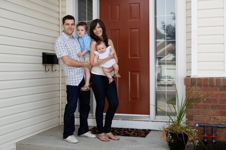 front of the house: Full length of happy couple standing with their kids in front of house Stock Photo