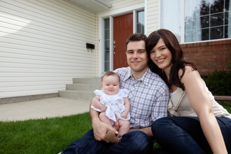 Portrait of couple with their adorable daughter sitting in front of house photo