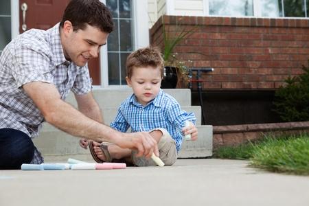 젊은 아버지는 아들이 옆에 앉아 바닥에 분필로 그리기 스톡 콘텐츠