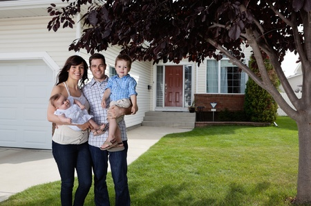 front door: Portrait of happy couple standing with their children in front of house