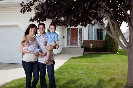 pareja en casa: Retrato de pareja feliz de pie con sus hijos delante de la casa Foto de archivo