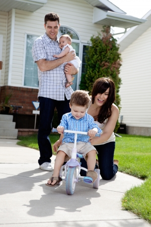 family bike: Cheerful mother teaching son to ride tricycle while husband holds daughter in background Stock Photo