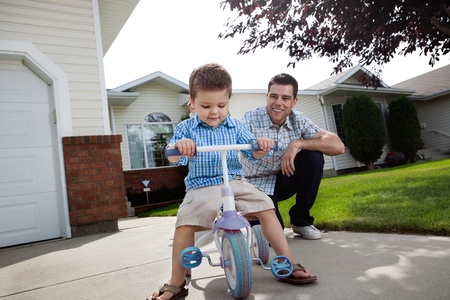 Happy father teaching his adorable son to ride a tricycle Stock Photo