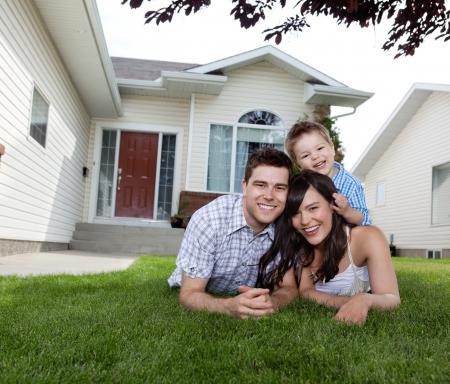 家族: 家の前に芝生の上に横たわって、幸せな家族の肖像画