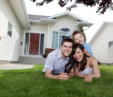 Portrait of happy family lying down on grass in front of house photo