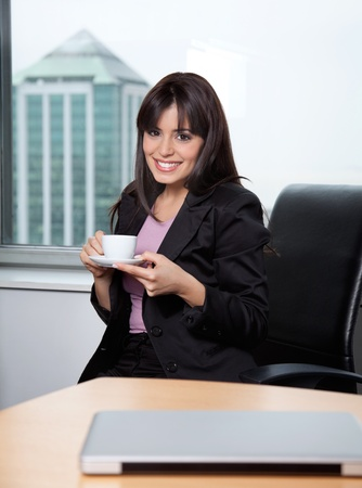 Portrait of smiling business woman having cup of coffee at office Stock Photo - 11702426