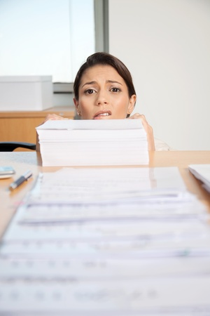 Head of businesswoman behind large pile of papers photo