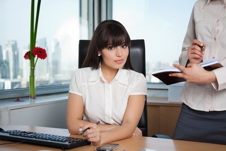 Portrait of female executive smiling with colleague standing beside her with calender photo