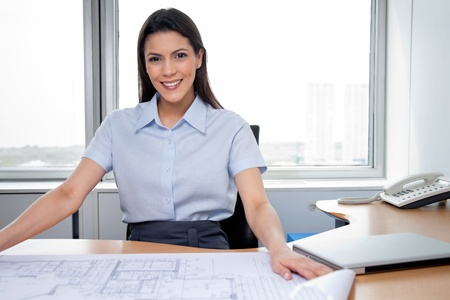 Portrait of pretty female architecture sitting with blueprints on desk photo