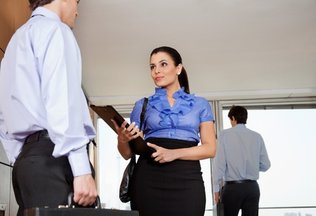 Low angle view of smart business .woman standing with her colleague in office photo