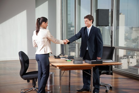 Professional business people shaking hands over a deal in office photo