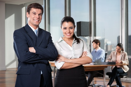 Portrait of business executives with arms crossed with colleagues working in background photo