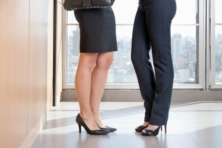 Niski sekcja dwóch kobiet menedżerów na wysokich obcasach stojÄ…c w biurze Zdjęcie Seryjne