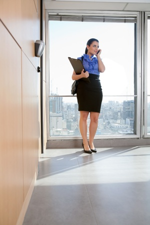 Full length of business woman talking on mobile phone photo