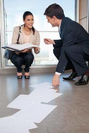recoger: Hombre de negocios ayudando bastante femenino recoger los papeles caídos