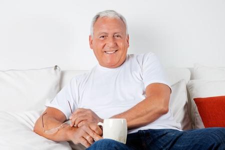 edad media: Retrato de hombre mayor relajado sentado en el sof� con la bebida caliente