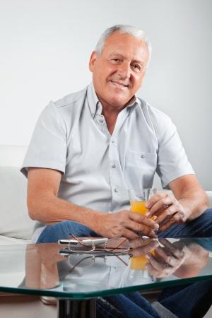 Portrait of casual senior man holding glass of orange juice photo