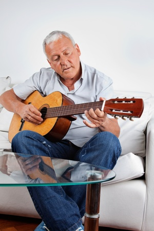 to sing: Senior man playing acoustic guitar at home