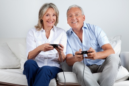 Happy senior couple playing video game at home photo