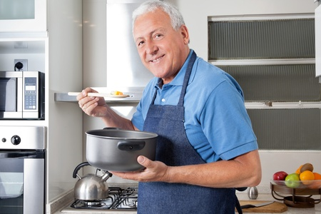 cooking utensils: Portrait of smiling senior man holding spoon to taste food