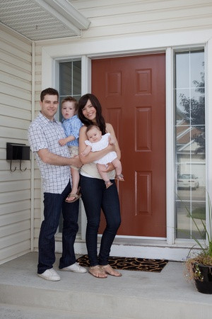 Portrait Of Sweet Family Standing In Front Of Their House. photo