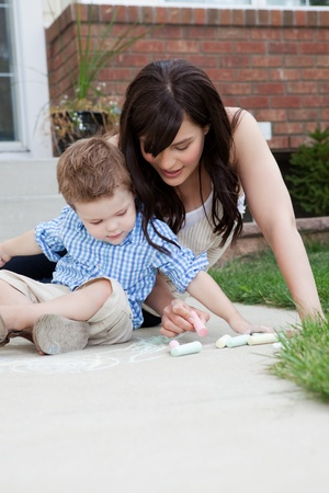 Young mother and son drawing on sidewalk with chalk photo