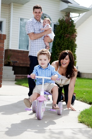 tricycle: Young happy boy riding tricycle with family watching Stock Photo