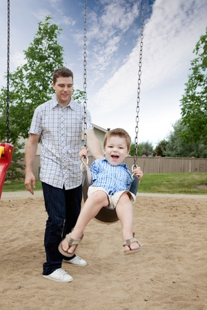 Happy Father Pushing Boy On Swing In Playground. photo